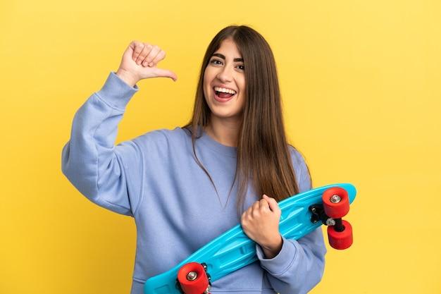 Jovem mulher caucasiana isolada em um fundo amarelo com um skate e uma expressão feliz