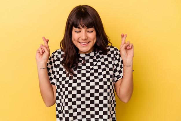 Jovem mulher caucasiana isolada em um fundo amarelo cruzando os dedos para ter sorte