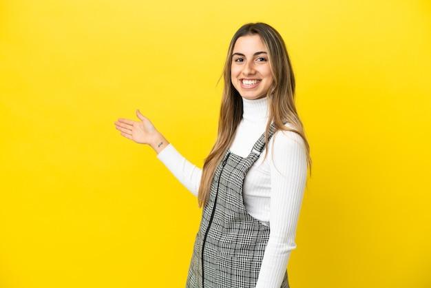 Jovem mulher caucasiana isolada em um fundo amarelo, estendendo as mãos para o lado para convidar para vir