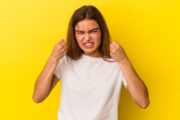 Jovem mulher caucasiana isolada em um fundo amarelo, mostrando o punho para a câmera, expressão facial agressiva.