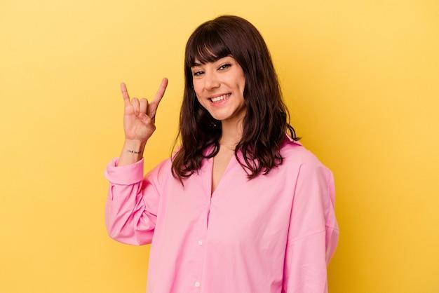 Jovem mulher caucasiana isolada em um fundo amarelo, mostrando um gesto de chifres como um conceito de revolução.