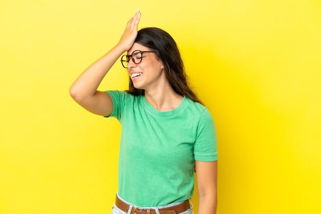 Jovem mulher caucasiana isolada em um fundo amarelo percebeu algo e pretende a solução