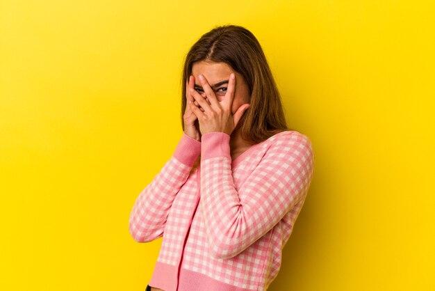 Jovem mulher caucasiana isolada em um fundo amarelo piscar por entre os dedos assustados e nervosos. Foto Premium