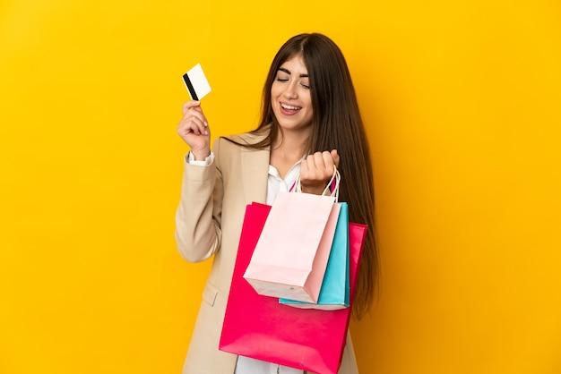 Jovem mulher caucasiana isolada em um fundo amarelo segurando sacolas de compras e um cartão de crédito