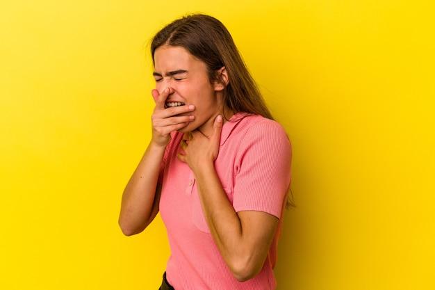 Jovem mulher caucasiana, isolada em um fundo amarelo, sofre de dor na garganta devido a um vírus ou infecção.