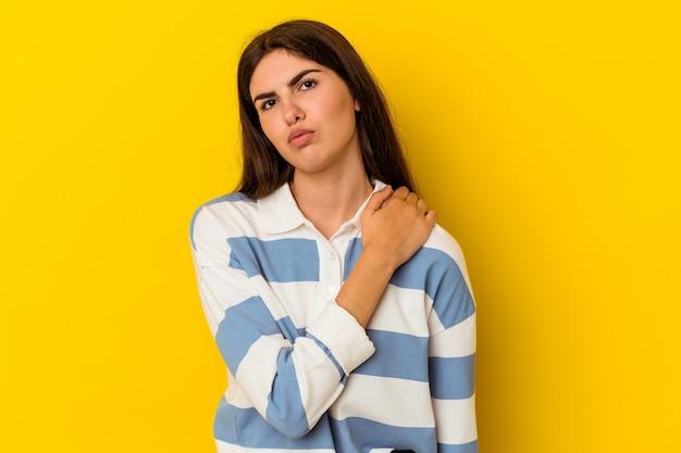 Jovem mulher caucasiana, isolada em um fundo amarelo, tendo uma dor no ombro.