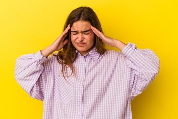 Jovem mulher caucasiana, isolada em um fundo amarelo, tocando as têmporas e tendo dor de cabeça.
