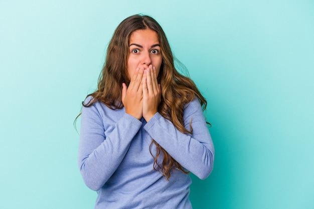 Jovem mulher caucasiana isolada em um fundo azul, cobrindo a boca com as mãos parecendo preocupadas.