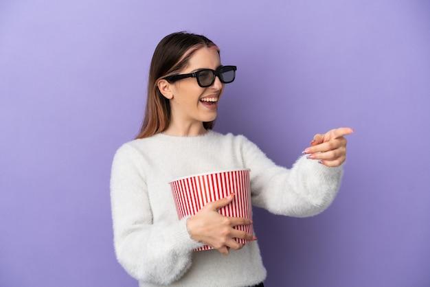 Jovem mulher caucasiana isolada em um fundo azul com óculos 3d e segurando um grande balde de pipocas enquanto aponta para longe