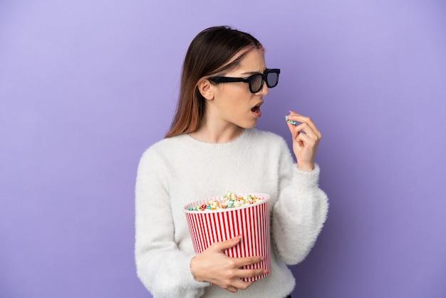 Jovem mulher caucasiana isolada em um fundo azul com óculos 3d e segurando um grande balde de pipocas enquanto olha para o lado