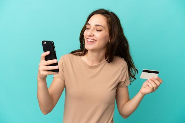 Jovem mulher caucasiana isolada em um fundo azul comprando com o celular com um cartão de crédito