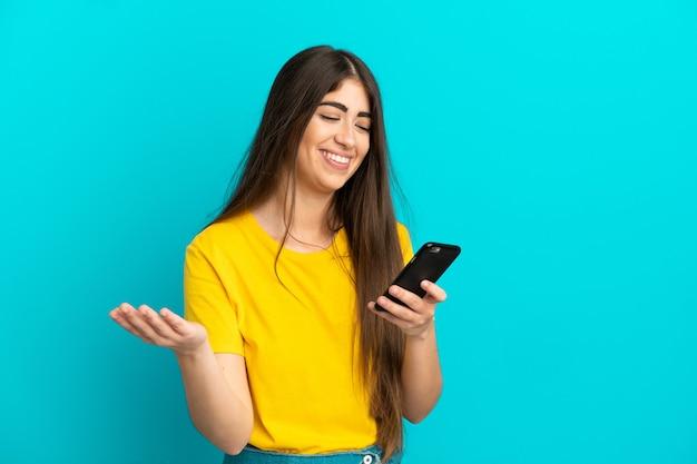 Jovem mulher caucasiana isolada em um fundo azul, conversando com alguém ao telefone celular