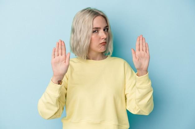 Jovem mulher caucasiana isolada em um fundo azul em pé com a mão estendida, mostrando o sinal de stop, impedindo você.