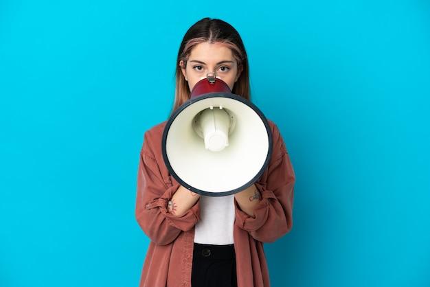 Jovem mulher caucasiana isolada em um fundo azul gritando em um megafone para anunciar algo
