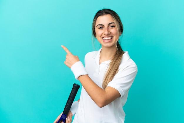 Jovem mulher caucasiana isolada em um fundo azul jogando tênis e apontando para a lateral