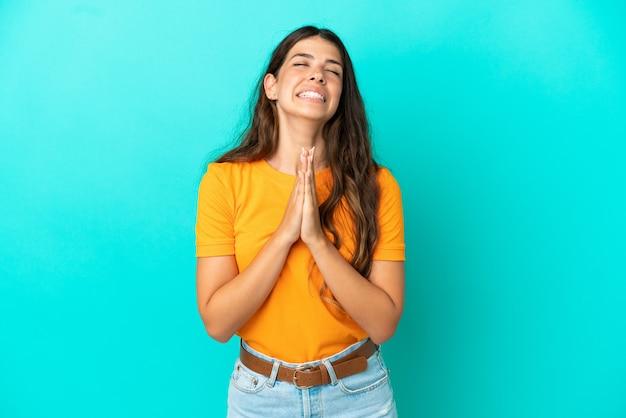 Jovem mulher caucasiana isolada em um fundo azul mantém as palmas das mãos juntas. pessoa pede algo
