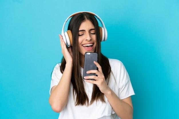 Jovem mulher caucasiana isolada em um fundo azul, ouvindo música com um celular e cantando