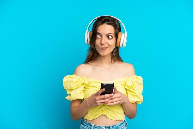 Jovem mulher caucasiana isolada em um fundo azul ouvindo música com um celular e pensando