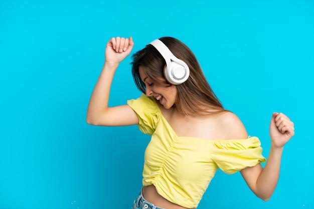 Jovem mulher caucasiana isolada em um fundo azul ouvindo música e dançando