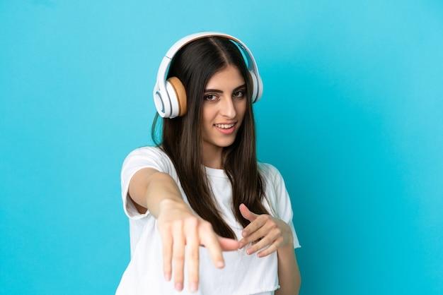 Jovem mulher caucasiana isolada em um fundo azul ouvindo música