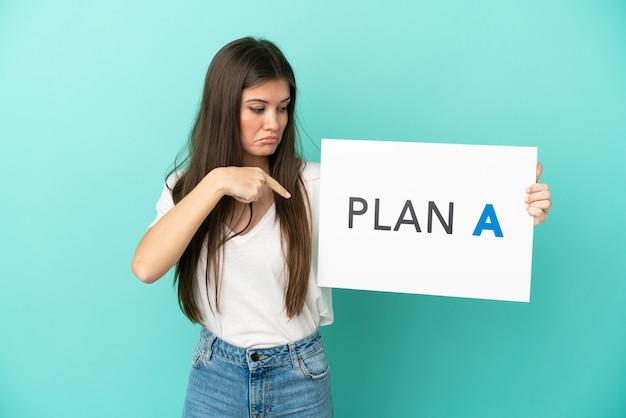 Jovem mulher caucasiana isolada em um fundo azul segurando um cartaz com a mensagem plano a e apontando-o
