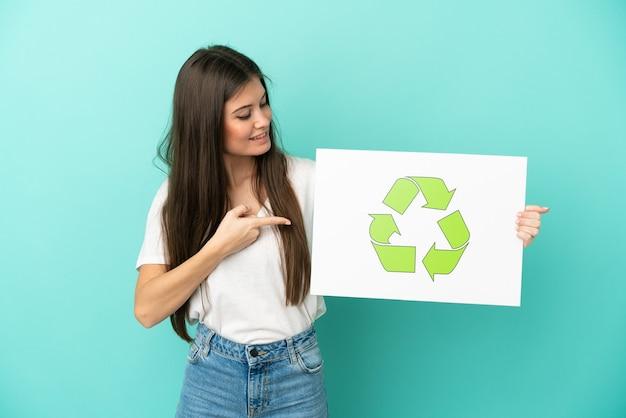 Jovem mulher caucasiana isolada em um fundo azul segurando um cartaz com o ícone de reciclagem e apontando-o