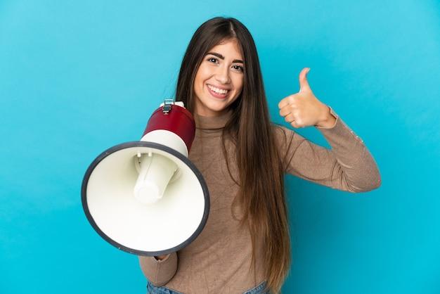 Jovem mulher caucasiana isolada em um fundo azul segurando um megafone com o polegar para cima