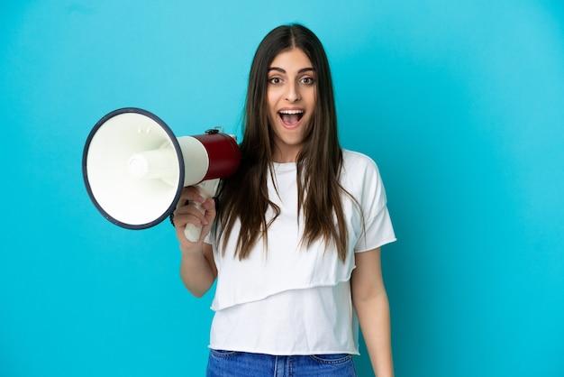 Jovem mulher caucasiana isolada em um fundo azul segurando um megafone e com expressão de surpresa