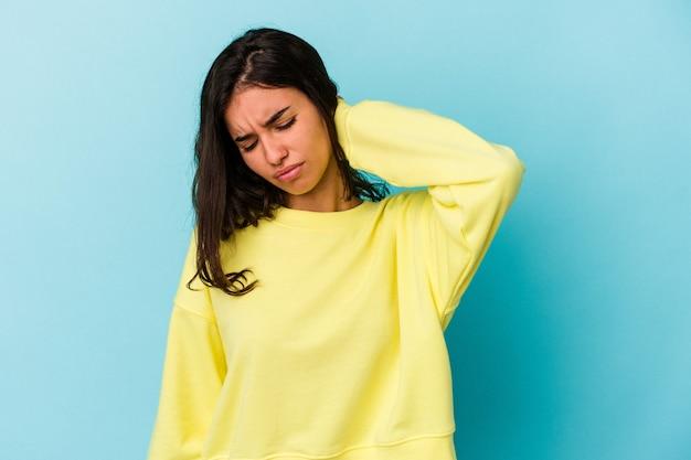 Jovem mulher caucasiana, isolada em um fundo azul, sofrendo de dores no pescoço devido ao estilo de vida sedentário.