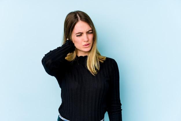 Jovem mulher caucasiana, isolada em um fundo azul, tendo uma dor no pescoço devido ao estresse, massageando e tocando com a mão.