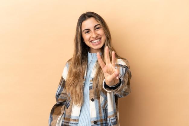 Jovem mulher caucasiana isolada em um fundo bege feliz e contando três com os dedos