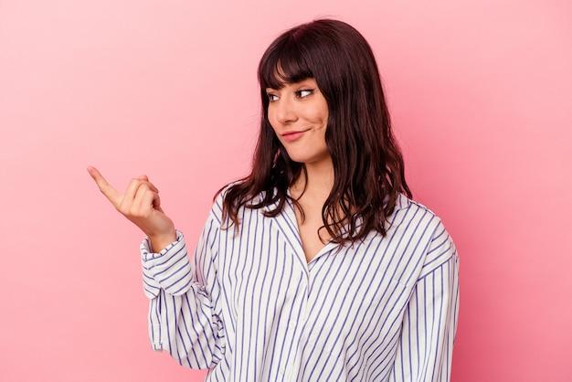 Jovem mulher caucasiana isolada em um fundo rosa, apontando com o dedo para você como se fosse um convite para se aproximar.