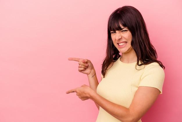 Jovem mulher caucasiana isolada em um fundo rosa apontando com os indicadores para um espaço de cópia, expressando entusiasmo e desejo.