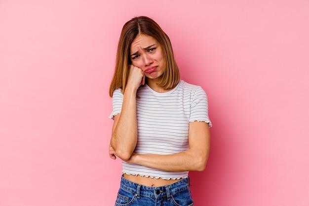 Jovem mulher caucasiana isolada em um fundo rosa, cansada de uma tarefa repetitiva.