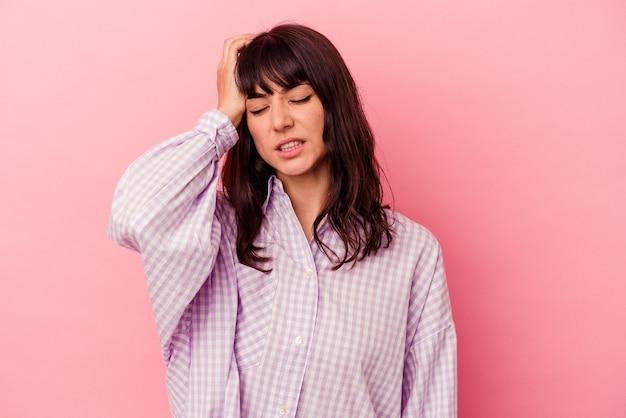 Jovem mulher caucasiana isolada em um fundo rosa cansada e com muito sono, mantendo a mão na cabeça.