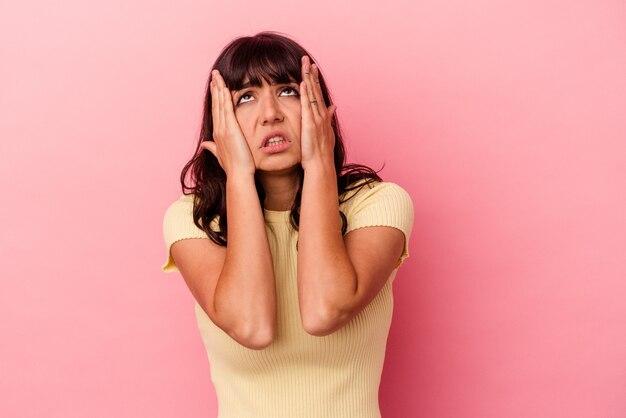 Jovem mulher caucasiana isolada em um fundo rosa, chorando e chorando desconsoladamente.
