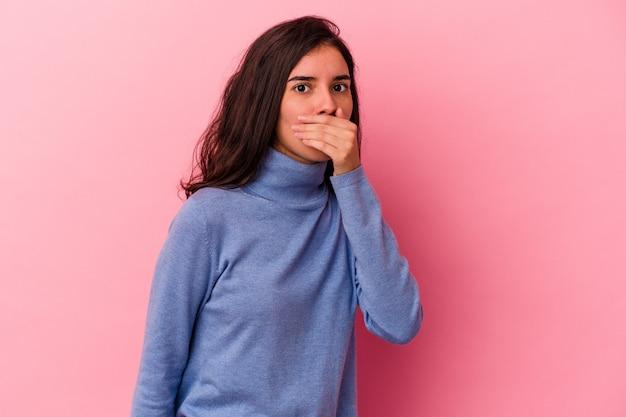 Jovem mulher caucasiana isolada em um fundo rosa, cobrindo a boca com as mãos parecendo preocupadas.
