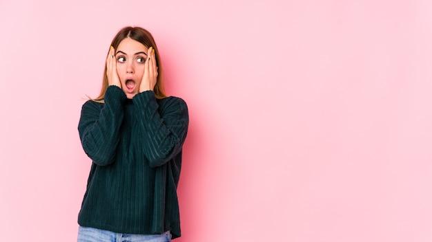 Jovem mulher caucasiana isolada em um fundo rosa, cobrindo as orelhas com as mãos, tentando não ouvir o som muito alto.