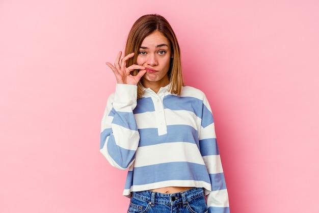 Jovem mulher caucasiana isolada em um fundo rosa com os dedos nos lábios, mantendo um segredo.