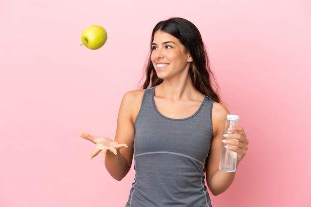 Jovem mulher caucasiana isolada em um fundo rosa com uma maçã e uma garrafa de água