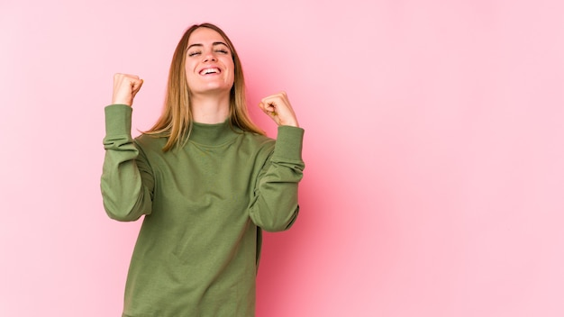 Jovem mulher caucasiana isolada em um fundo rosa, comemorando uma vitória, paixão e entusiasmo, expressão feliz.
