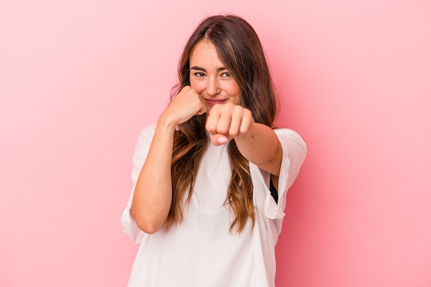 Jovem mulher caucasiana isolada em um fundo rosa dando um soco, raiva, lutando devido a uma discussão, boxe.