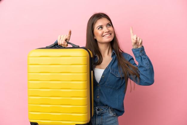 Jovem mulher caucasiana isolada em um fundo rosa de férias com mala de viagem e apontando para cima