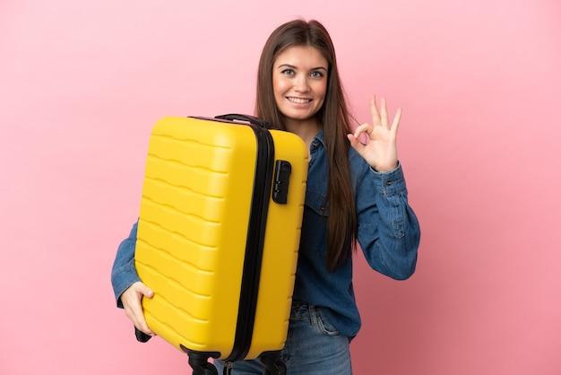 Jovem mulher caucasiana isolada em um fundo rosa de férias com mala de viagem e fazendo sinal de ok