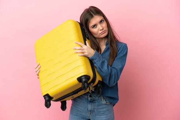 Jovem mulher caucasiana isolada em um fundo rosa de férias com mala de viagem e infeliz