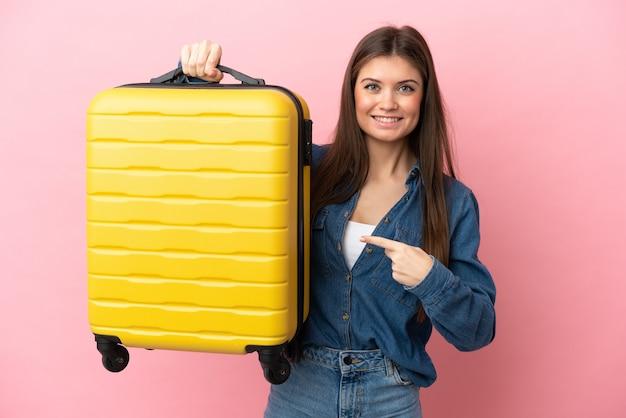 Jovem mulher caucasiana isolada em um fundo rosa de férias com mala de viagem