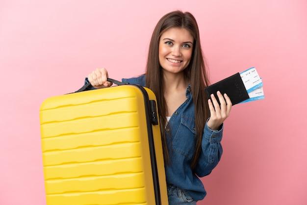 Jovem mulher caucasiana isolada em um fundo rosa de férias com mala e passaporte