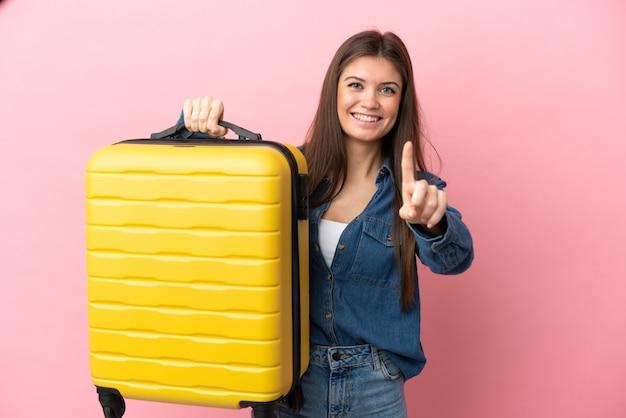 Jovem mulher caucasiana isolada em um fundo rosa de férias com uma mala de viagem e contando uma