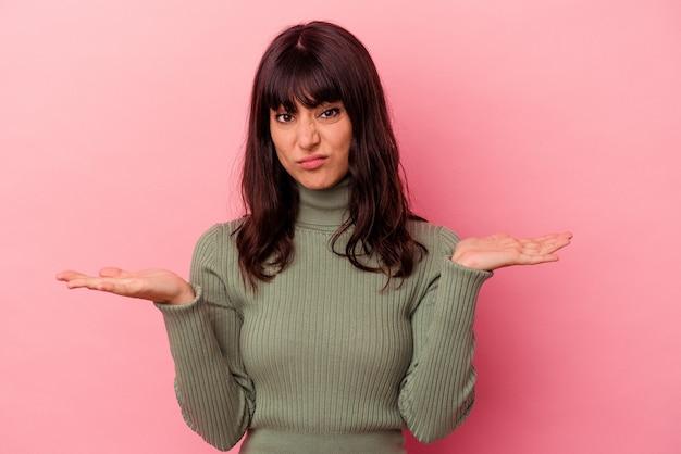 Jovem mulher caucasiana isolada em um fundo rosa duvidando e encolhendo os ombros os ombros em gesto de questionamento.