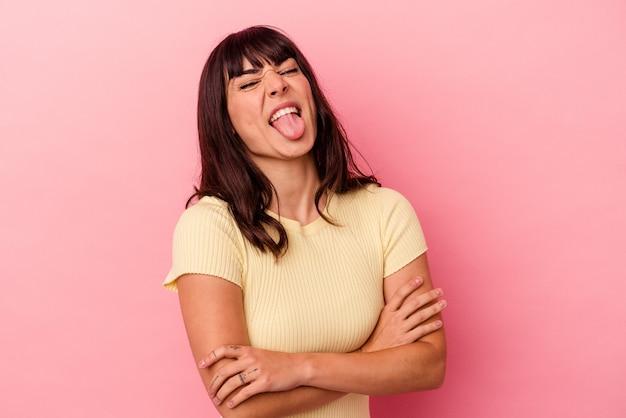 Jovem mulher caucasiana isolada em um fundo rosa engraçado e amigável, mostrando a língua.